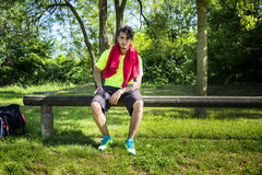 Athletic young man resting in city park Stock Photos