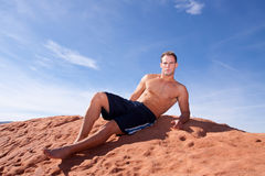 Athletic young man resting on the rocks Stock Photo