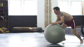 Athletic young man rolling on a fitness ball, practicing balancing stock video footage