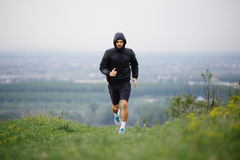Athletic young man running during autumn, winter morning. Healthy lifestyle Royalty Free Stock Images