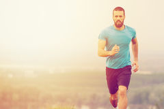 Athletic young man running during autumn, winter morning. Royalty Free Stock Images