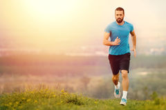Athletic young man running during autumn, winter morning. Stock Images