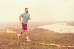 Athletic young man running during autumn, winter morning. Healthy lifestyle Royalty Free Stock Photos