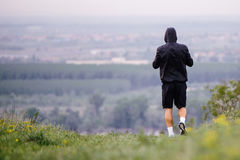 Athletic young man running during autumn, winter morning. Healthy lifestyle. Athletic runner doing stretching exercise, preparing for running in the nature with Royalty Free Stock Images