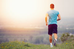 Athletic young man running in the nature. Stock Image