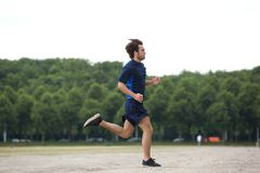 Athletic young man running outdoors. Full body side view of an athletic young man running outdoors royalty free stock image