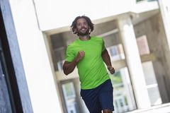Athletic young man running and working out in the city. Athletic young man running and working out in urban enviroment Royalty Free Stock Images