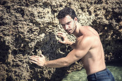 Athletic young man in the sea or ocean by rocks Stock Photography