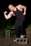 Athletic young man in the slums at night. Pumped white guy posing in the backyard Stock Image