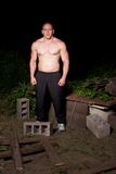 Athletic young man in the slums at night. Pumped white guy posing in the backyard Royalty Free Stock Images