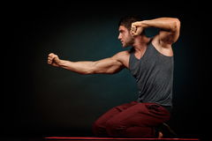 Athletic young man in studio with dark background Stock Images