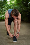 Athletic Young Man Tying his Shoelace. At the Park While Doing Outdoor Fitness Training Stock Photos
