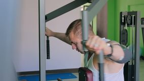 Athletic young man using exercise machine at gym stock video footage