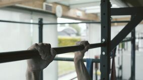 Athletic man working out at the gym and doing pull-ups
