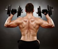 Athletic young man working with heavy dumbbells Royalty Free Stock Photo