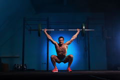 Athletic young man working out with barbell in gym Royalty Free Stock Image
