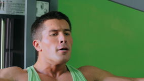 Athletic young man working out on fitness exercise equipment at gym stock video