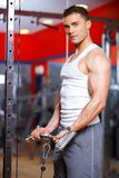 Athletic young man working out in a gym Stock Photos