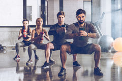Athletic young people in sportswear with dumbbells exercising at the gym Royalty Free Stock Image