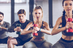 Athletic young people in sportswear with dumbbells squatting and exercising at the gym Stock Photo
