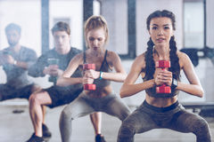 Athletic young people in sportswear with dumbbells squatting and exercising at the gym Royalty Free Stock Photos