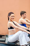 Athletic young people using a rower Royalty Free Stock Images