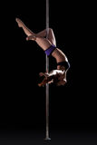 Athletic young pole dancer, isolated on black Royalty Free Stock Images