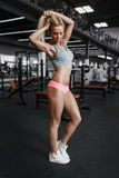 Athletic young sexy blonde girl posing in the gym and Stock Photos