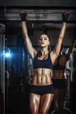 Athletic young girl pulls up on bar in the gym stock images