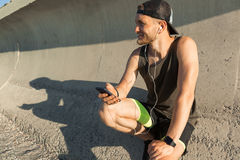 Athletic young sportsman listening to music with earphones Stock Photos