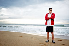 Athletic young sportsman resting after intensive morning jogging standing on the beach Royalty Free Stock Photo