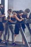 Athletic young sportswoman running on treadmill at the gym. Fitness couple gym concept Royalty Free Stock Photos