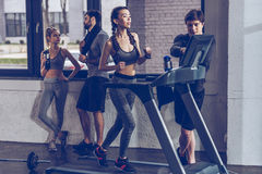 Athletic young sportswoman running on treadmill at the gym. Fitness couple gym concept Stock Images