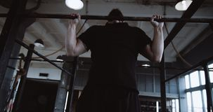 Athletic young strong handsome Caucasian man doing pull-ups during functional workout in large gym slow motion. Healthy lifestyle and motivation for success stock footage
