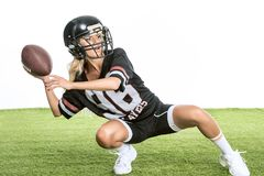 athletic young woman in american football uniform throwing ball while sitting squats on grass
