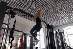 Athletic young woman with a beautiful body in black clothes in sneakers hangs on a modern simulator in the sport class. royalty free stock photo