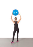 Athletic young woman with blue ball Royalty Free Stock Photos