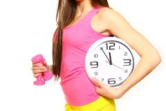 Athletic young woman with a clock and dumbbells Stock Photography