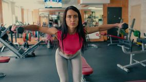 Athletic young woman doing exercises with dumbbells in the gym. 4 k. Young beautiful sporty girl brunette with long hair doing exercises with dumbbells in the stock footage