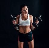 Athletic young woman doing a fitness workout against black background. Attractive fitness girl pumping up muscles with dumbbells. stock image