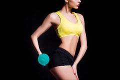 Athletic young woman doing a fitness workout with dumbbells on black studio background Royalty Free Stock Image