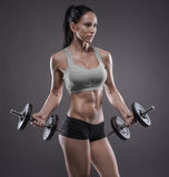 Athletic young woman doing a fitness workout with dumbbells on g Royalty Free Stock Photo