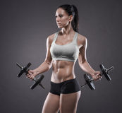 Athletic young woman doing a fitness workout with dumbbells on g Stock Image