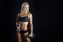 Athletic young woman doing a fitness workout with dumbbels. Athletic young girl smiling doing a fitness workout with dumbbells isolated on black background royalty free stock photography