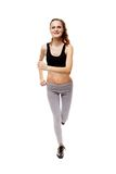 Athletic young woman doing jogging. Full length studio shot of an athletic young woman running isolated over white background Stock Images