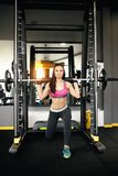 Athletic young woman doing lunges with the smith machine. stock photos