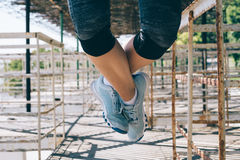 Athletic young woman doing pull-ups in the morning outdoors, close-up. Female legs in blue sneakers stock images