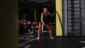 Athletic young woman doing some crossfit exercises with a rope. Dark area stock video