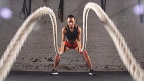 Athletic young woman doing some crossfit exercises with a rope indoor. Slow motion stock footage