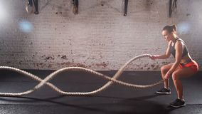 Athletic young woman doing some crossfit exercises with a rope indoor. Slow motion.